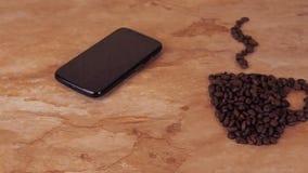 Een kop van koffiebonen en een mobiele telefoon Op de keuken marmeren lijst het teken van een kop koffiebonen en mobiel stock footage