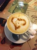 Een Kop van koffiecappuccino met een hart van kaneel op de lijst in de koffie stock foto's