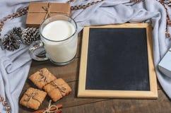 Een kop van melk, pijpjes kaneel, eigengemaakte koekjes en een lei in Kerstmisdecor stock foto