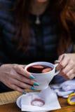 een kop van rode die wijn in handen wordt gehouden royalty-vrije stock afbeeldingen