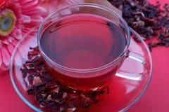 Een kop van rode karkade met bladeren van thee Stock Afbeelding