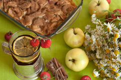 Een kop van sterke zwarte thee met een citroenplak, een appeltaart, een boeket van kamilles, pijpjes kaneel, rijpe appelen en rij Royalty-vrije Stock Fotografie