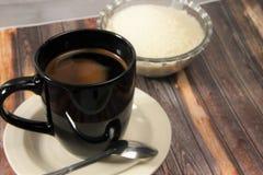 Een kop van zwarte koffie, bruine achtergrond stock afbeeldingen