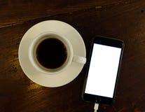 Een kop van zwarte koffie met mobiele telefoon stock foto's