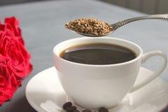 Een Kop van zwarte koffie op de lijst, een boeket van rode rozen stock afbeelding