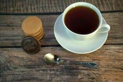 Een kop van zwarte thee op een porseleinschotel, een lepel en een stapel sponskoekjes met chocolade, ligt op een houten lijst royalty-vrije stock afbeeldingen