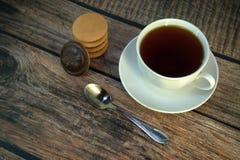 Een kop van zwarte thee op een porseleinschotel, een lepel en een stapel sponskoekjes met chocolade, ligt op een houten lijst royalty-vrije stock afbeelding