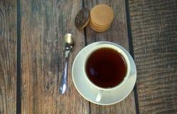 Een kop van zwarte thee op een porseleinschotel, een lepel en een stapel sponskoekjes met chocolade, ligt op een houten lijst stock afbeeldingen