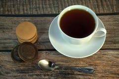 Een kop van zwarte thee op een porseleinschotel, een lepel en een stapel sponskoekjes met chocolade, ligt op een houten lijst stock afbeelding