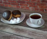 Een kop van zwarte thee op een schotel en een plaat met twee donuts in chocoladesuikerglazuur en stukken van bize, liggen op een  stock afbeeldingen