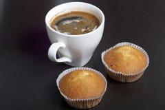 Een kop vers gebrouwen koffie en muffins stock afbeelding