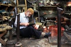 Een koperslager die druk een kopercontainer in bazaar de van Urfa (Sanliurfa) maken in oostelijk Turkije Stock Fotografie