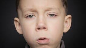 Een koud jongensclose-up op een zwarte achtergrond stock video