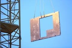 Een kraan heft de plaat op om een huis te bouwen royalty-vrije stock fotografie