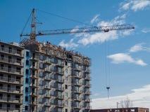 Een kraan voor bouw van een gebouw met meerdere verdiepingen Stock Foto's