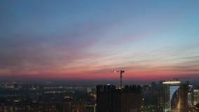 Een kraan werkt in de stad tegen een zonsondergangachtergrond stock footage