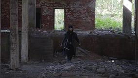 Een krachtige gebaarde kerel in een regenjas en een hoed loopt door een verlaten fabriek en verslaat de stappen aan het lagere ni stock footage