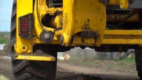 Een krachtige gele tractor drijft langs een landweg, langzame motie stock videobeelden
