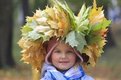 Een kroon van gele bladeren op het hoofd van het meisje stock afbeelding