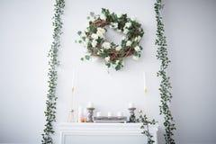 Een kroon van rozen hangt over de open haard stock afbeelding