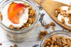 Een kruik die met granola en yoghurt wordt gevuld en een kruik fiiled met gran Royalty-vrije Stock Foto
