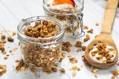 Een kruik die met granola en yoghurt wordt gevuld en een kruik fiiled met gran Stock Foto