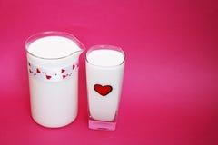 Een Kruik en een glas melk op roze achtergrond, Melkconcept Stock Foto's