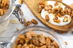 Een kruik fiiled met granola, houten lepelwhit granola, op witte wo Stock Foto's