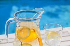 Een kruik ijskoud water met citroen en sinaasappel Stock Fotografie