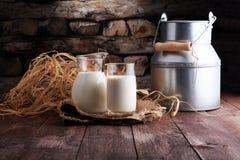 Een kruik melk en glas melk op een houten lijst stock foto's