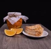 Een kruik oranje stroop met oranje plakken naast een plaat van gebraden pannekoeken op een houten oppervlakte met een zwarte acht royalty-vrije stock afbeelding