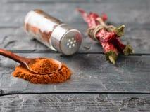 Een kruik van Spaanse peper van de peulen aan de zwarte lijst Stock Foto