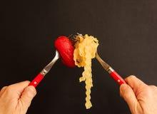 Een kruising van twee vorken met noedels en tomaat Stock Foto