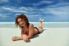 Een krullend meisje op het strand Stock Afbeeldingen