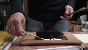 Een kunstenaar die de helft van een gouden blad voor het behandelen van een pictogram nemen stock footage