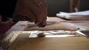 Een kunstenaar die een gouden blad voor een dekking op een pictogram drukken stock video