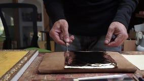 Een kunstenaar die een gouden blad voor het behandelen van een pictogram snijden stock videobeelden
