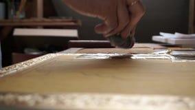 Een kunstenaar in zijn studio, die een gouden blad voor een dekking op een pictogram drukken stock footage