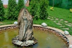 Een kunstmatige tuinfontein met een grote kom stock foto's