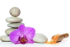 Een kuuroord met stenen, een orchideebloem en een spatel met zout op een wit wordt geplaatst dat Stock Foto