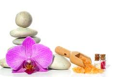 Een kuuroord met stenen, een orchideebloem en een spatel met zout op een witte achtergrond wordt geplaatst die Stock Foto's