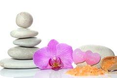 Een kuuroord voor Valentijnskaartendag wordt geplaatst met stenen, een orchideebloem en een spatel met zout op een witte achtergr Royalty-vrije Stock Fotografie