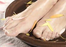 Een kuuroordsamenstelling met een kom en vrouwelijke voeten Royalty-vrije Stock Afbeeldingen