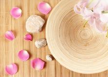 Een kuuroordsamenstelling van bloemblaadjes, stenen en bamboe Stock Foto