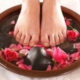 Een kuuroordsamenstelling van voeten, stenen en bloemblaadjes Stock Foto's