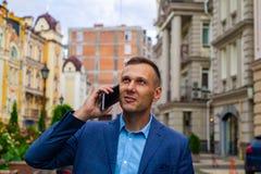 Een kwade en knappe zakenman in een stad die telefonisch spreken royalty-vrije stock foto's