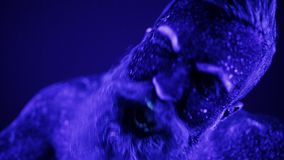 Een kwade mens met een baard in het ultraviolette licht gilt frighteningly stock footage