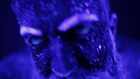 Een kwade mens met een baard in het ultraviolette licht gilt frighteningly Een vreselijke gebaarde mens in ultraviolet stock footage