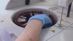 Een laboratoriumarbeider die een bloedonderzoek doen laadt de buizen in de machine De hulplading het flesje in het laboratorium stock videobeelden