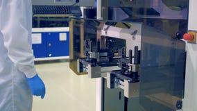 Een laboratoriumarbeider zet een zonnediemodulemateriaal in een transportbandmachine bij een moderne fabrieksvloer wordt geplaats stock footage